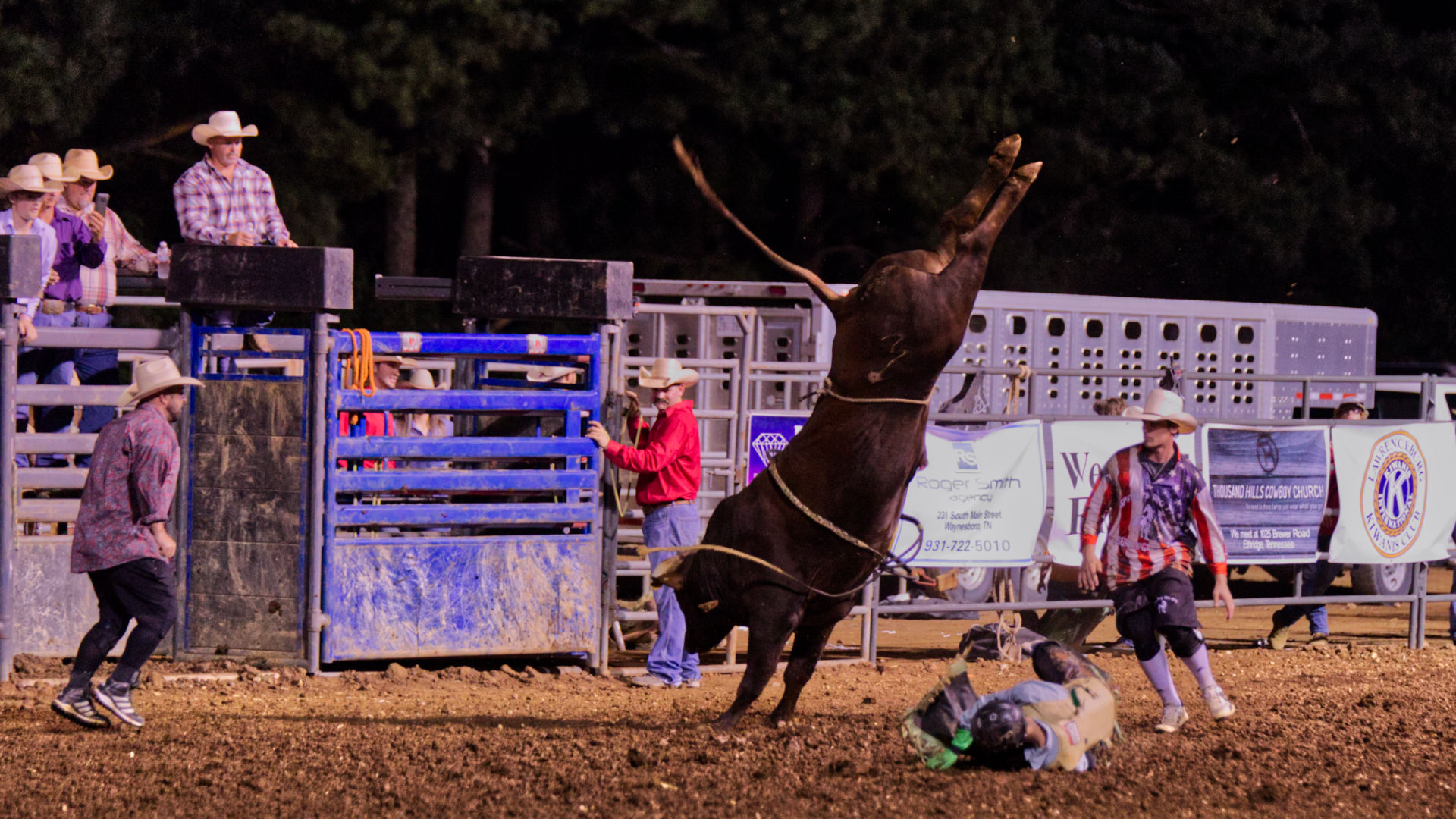 A bull in full kick at a rodeo.