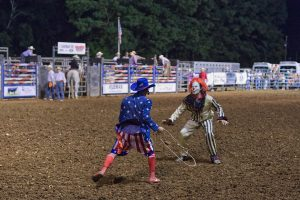 Two rodeo clowns about to wrestle.