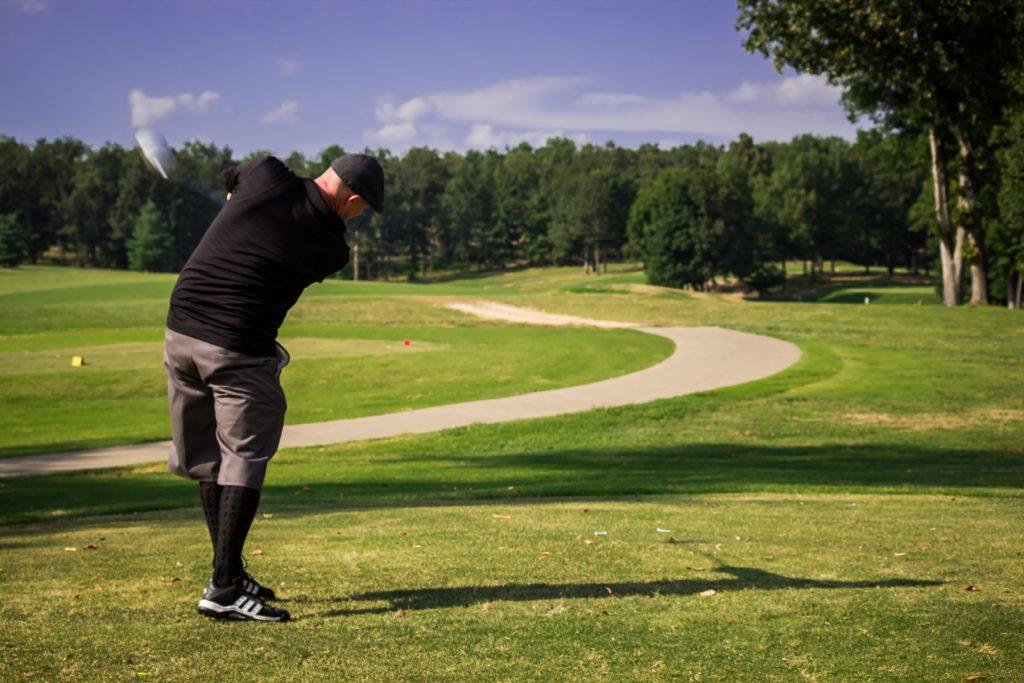Man swinging golf club wearing traditional golf attire.