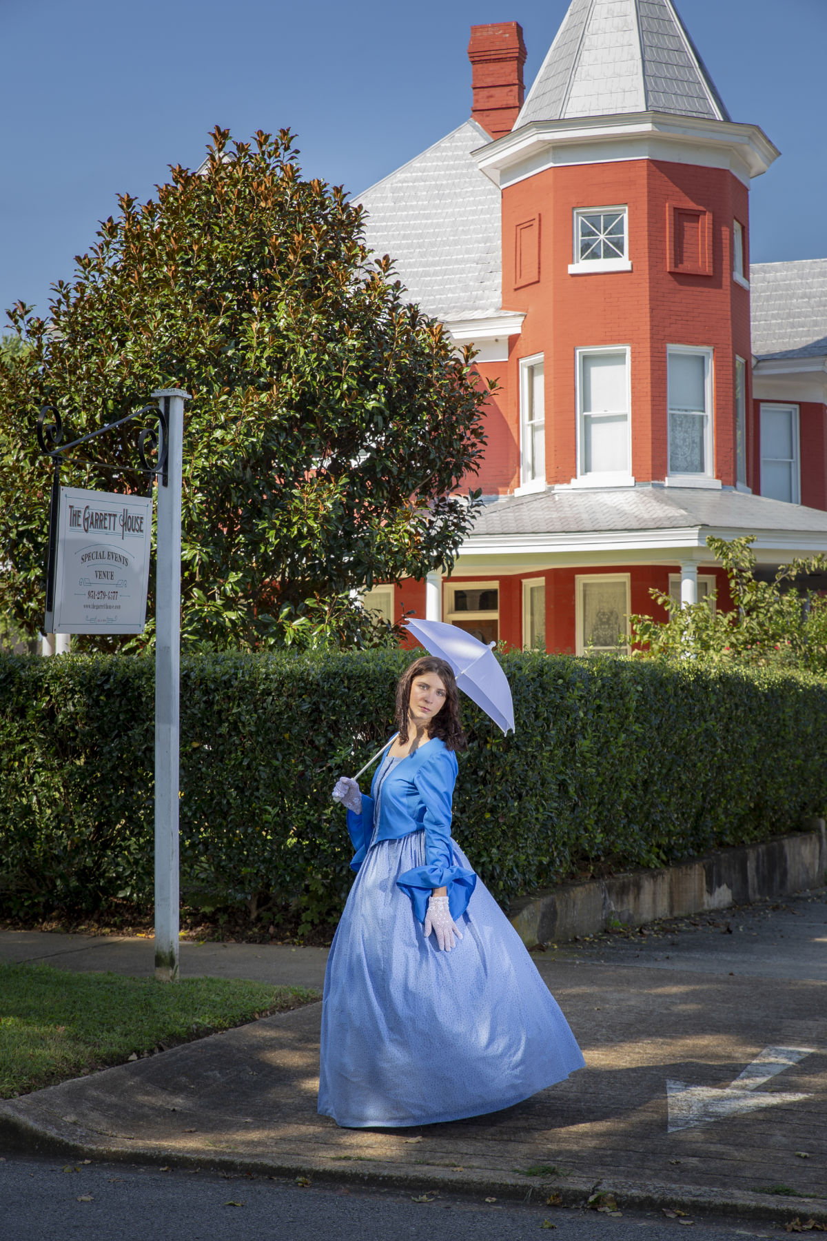 Girl with umbrella in front of victorian house.