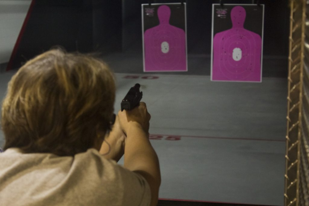 Lady firearm shooter indoors at range.